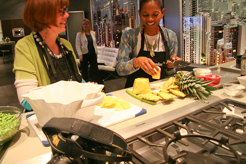 Tabitha chopping pineapple as Susan watches