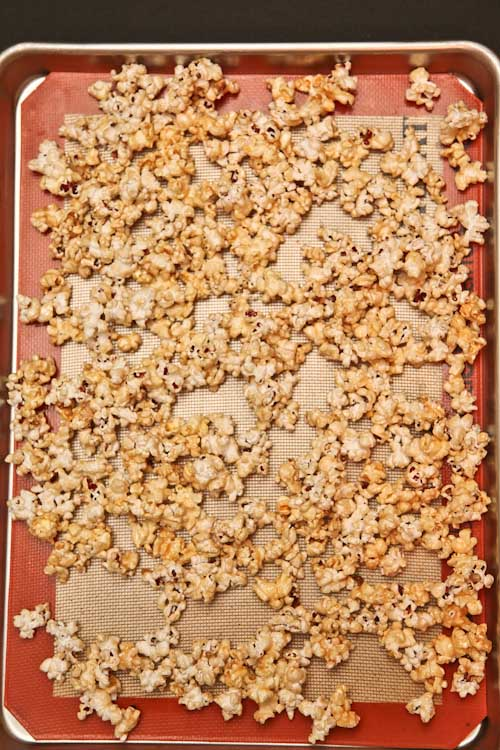 spread the popcorn evenly on the baking sheet in one layer