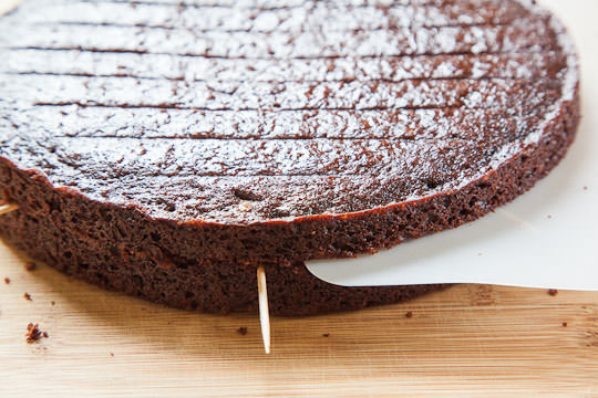 Remove the top layer of the cake using a thin flexible plastic cutting board or a piece of stiff cardboard.