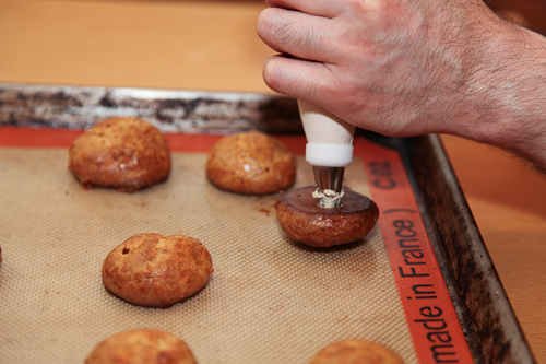 piping the gougeres with goat cheese