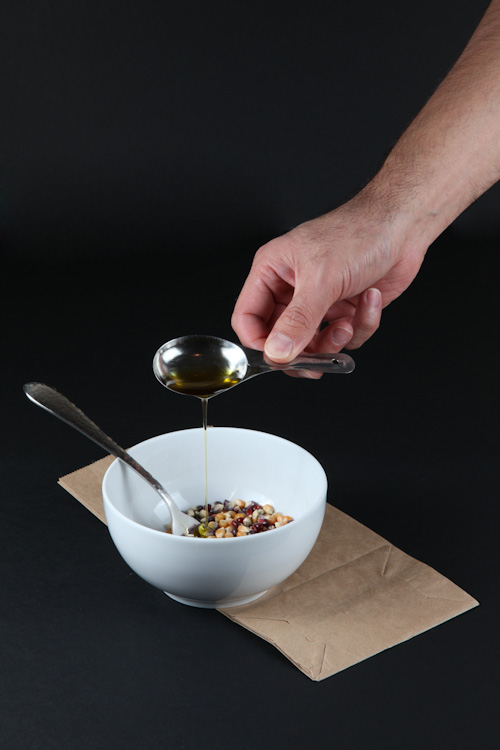Place the popcorn in a small bowl and pour the olive oil over it.