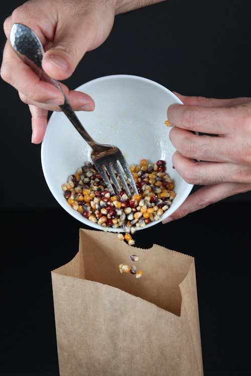 Pour the coated popcorn into a kraft paper bag, the kind you bring your lunch in.