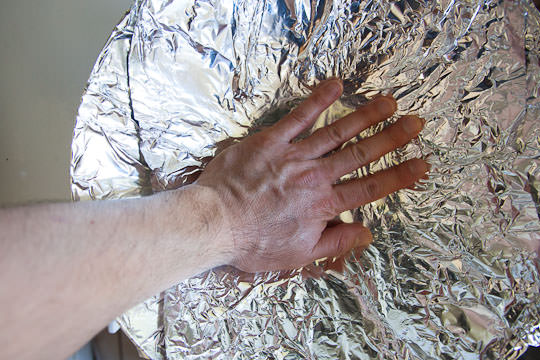 Lay another piece of foil crosswise to cover the entire wok. Again make sure the foil touches the bottom of the wok. Photo by Irvin Lin of Eat the Love. www.eatthelove.com