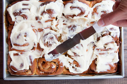 Spread the cream cheese frosting over the cooled sweet potato cinnamon rolls. Process photo by Irvin Lin of Eat the Love.
