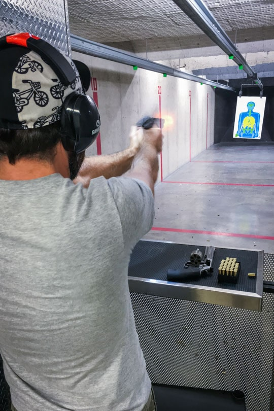 AJ firing a gun.