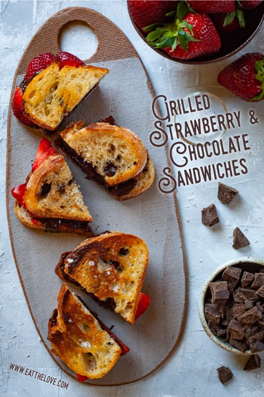 Grilled strawberry and chocolate sandwiches on sourdough crusty bread and a sprinkling of sea salt sitting on a cheeseboard.