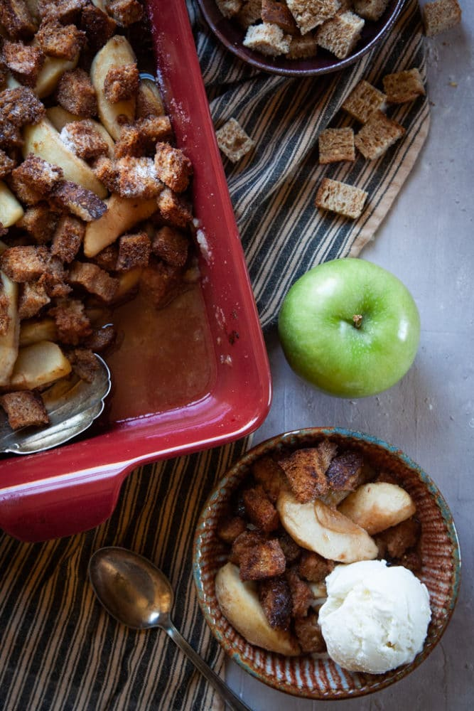 Apple Brown Betty Dessert on a table, served with a scoop of vanilla ice cream.