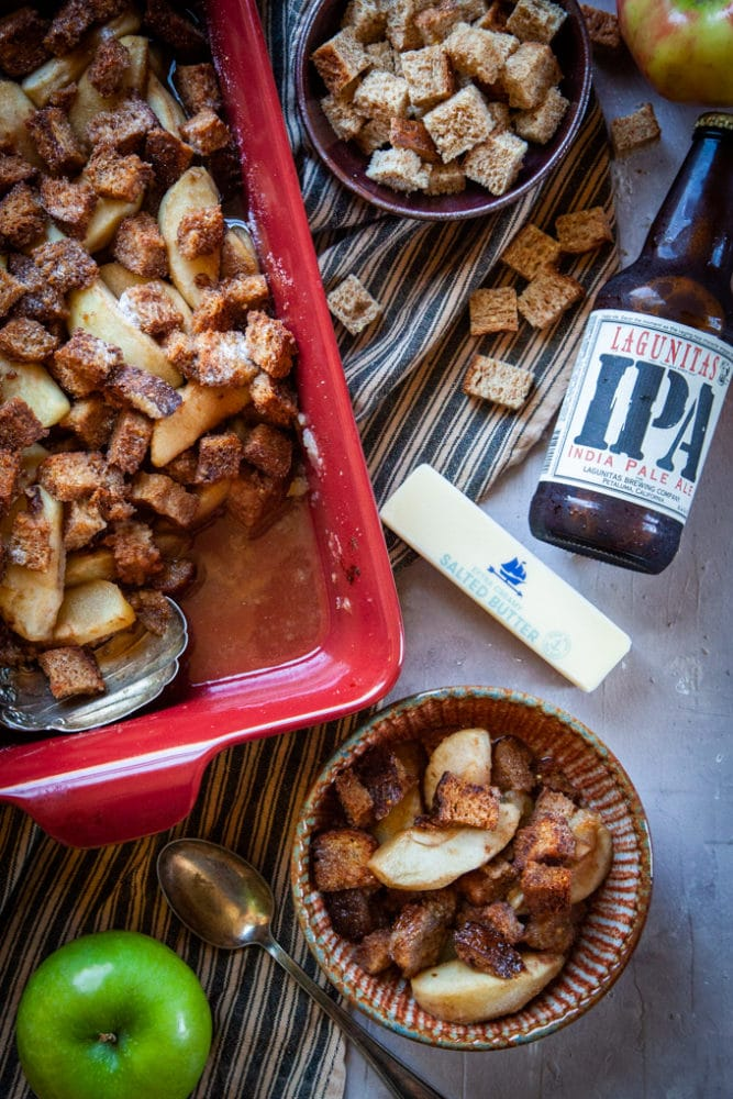 Apple Brown Betty with IPA Beer on a table with ingredients that make up the recipe, including apples, butter, bread cubes and beer.