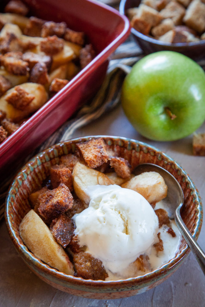 A scoop of vanilla bean ice cream in a bowl of Apple Brown Betty, a traditional rustic American dessert