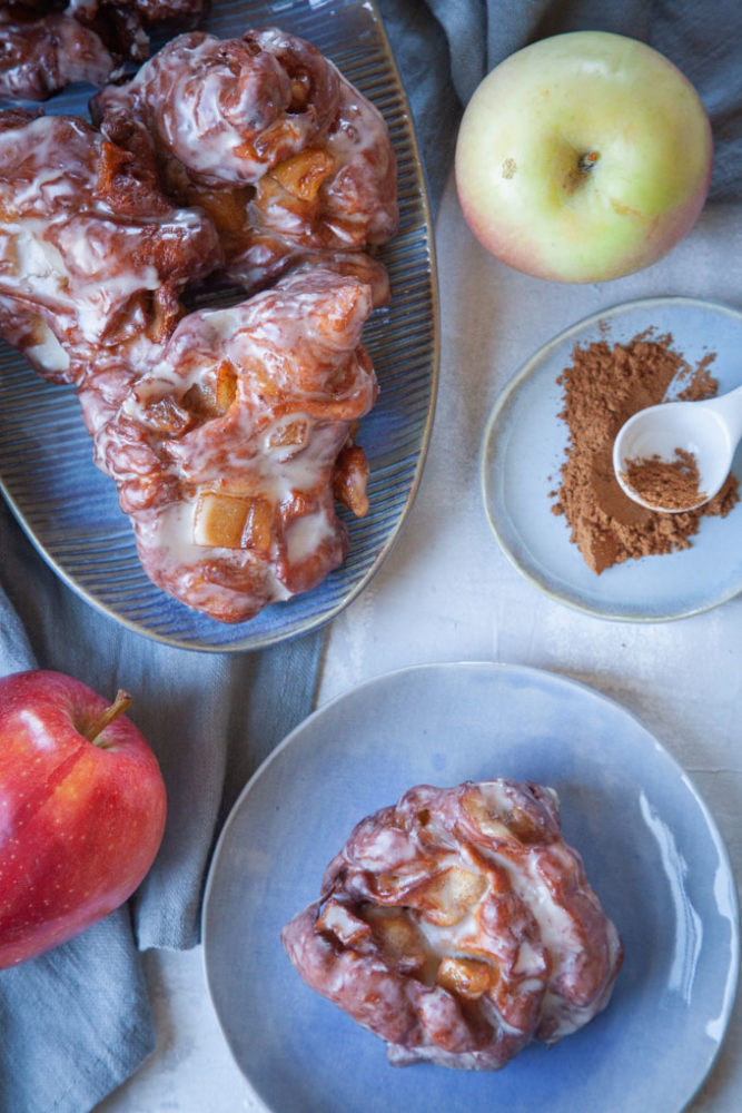 Apple Fritters on two plates, surrounded by apples and cinnamon.