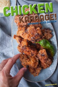 Chicken karaage, japanese fried chicken, piled on a plate with a hand reaching to grab a piece.