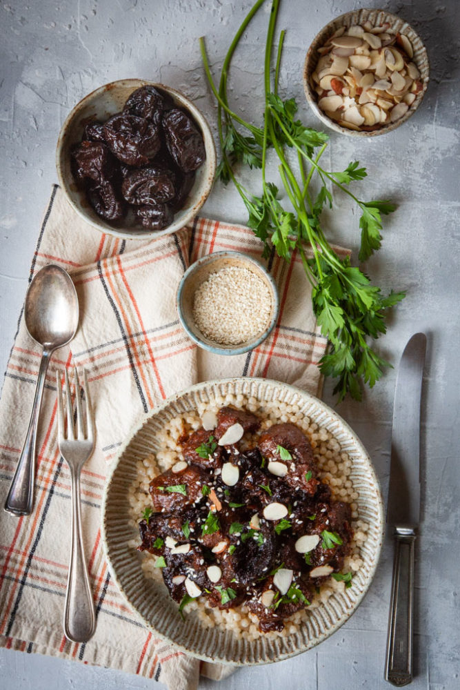 Traditional Moroccan lamb tagine with prunes in a ceramic bowl surrounded by ingredients in prep bowls.