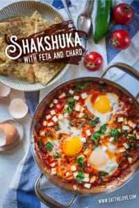 Shakshuka, a thick tomato sauce dish with eggs cooked directly in it, sitting on a table with a bowl of toasted pita on the side.