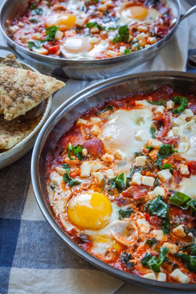 two pans with Shakshuka, a thick tomato sauce dish with eggs cooked directly in it, sitting on a table with a bowl of toasted pita on the side.