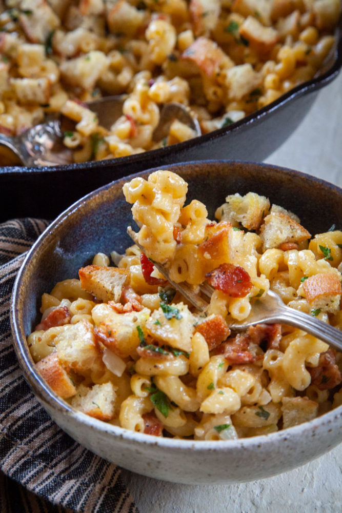 a fork filled with homemade baked mac and cheese with bacon over a bowl of the mac and cheese and a skillet in the background, filled with the bacon mac and cheese.