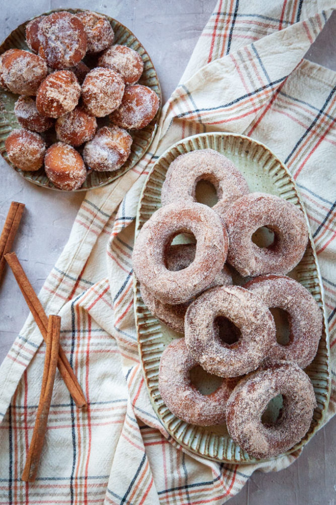 A pile of apple cider donuts on a plate, with a smaller plate of donut holes.