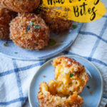 Fried Mac and Cheese Bites on a plate, with one mac and cheese ball open to see the gooey cheese inside.
