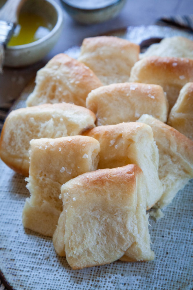 Overnight Parker House Rolls piled up on a serving plate.