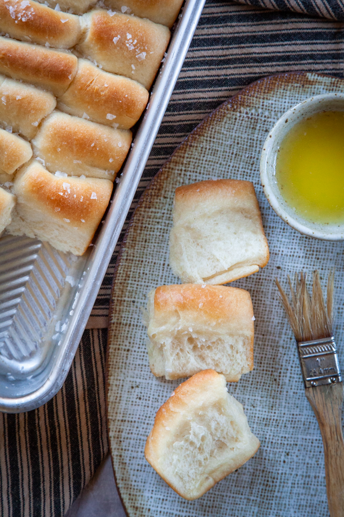 Parker House dinner rolls on a serving plate with a brush and small bowl of melted butter.