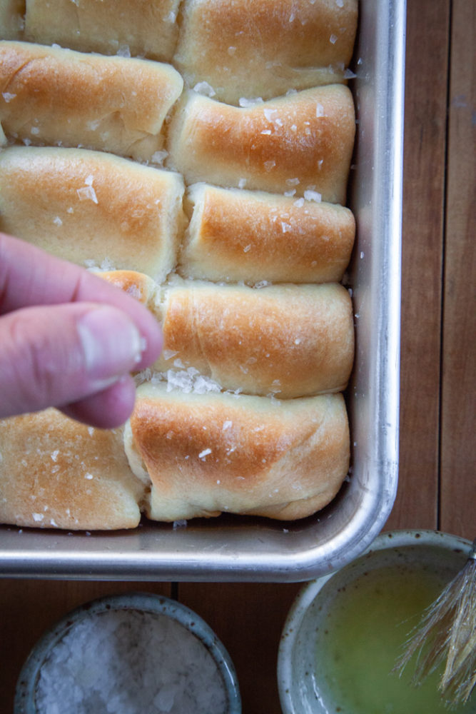 Sprinkling finishing salt on just baked Parker House Rolls.