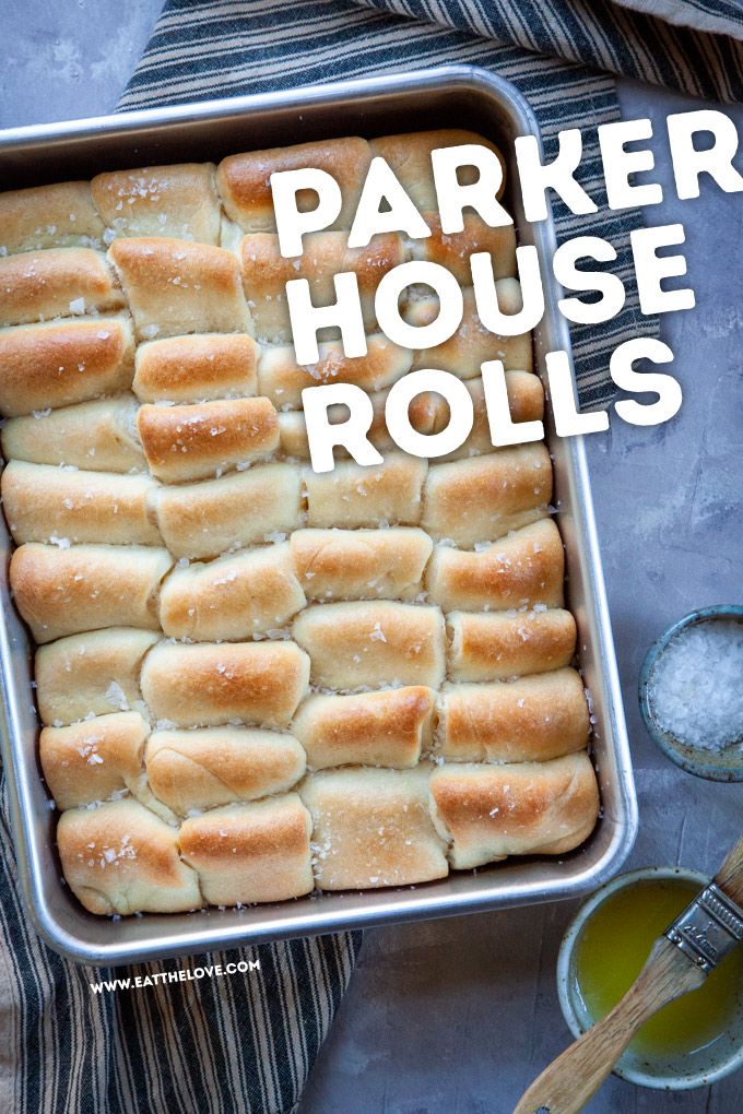 Fresh baked Parker House rolls in a pan sitting on a table with melted butter and flaky salt in small bowls next to baking pan.