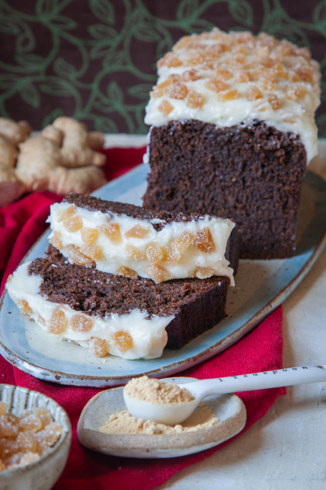 Sliced gingerbread stout cake next to fresh ginger root, candied ginger and ground ginger.