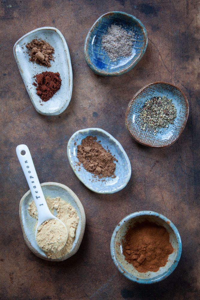 Various warm wintery spices on small dishes, like cinnamon, cardamom, nutmeg, ginger, allspice, cloves, black pepper.