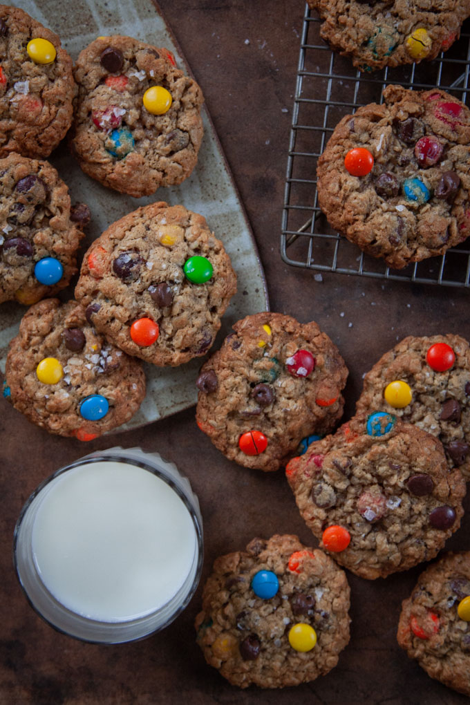 The best monster cookies on a table with a glass of milk.