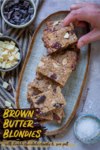 A hand reaching out to grab a brown butter blondie from a plate of blondies, surrounded by chopped chocolate.