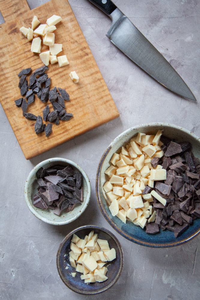 Chopped white and dark chocolate on a cutting board and bowls.
