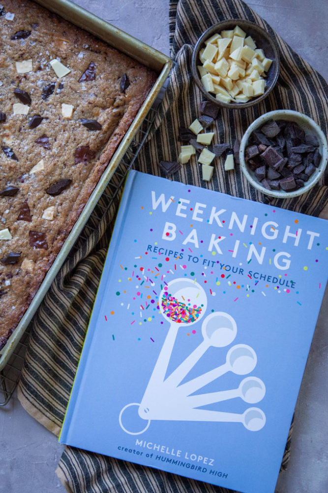 The cookbook Weeknight Baking next to a pan of Brown Butter Blondies, a recipe adapted from the book.