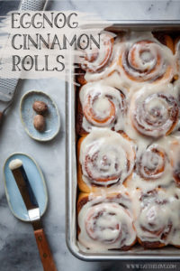 Eggnog Cinnamon Rolls in a pan, next to nutmeg and an offset spatula used to spread the bourbon cream cheese glaze.