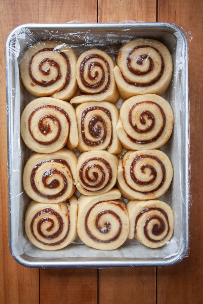 Eggnog cinnamon rolls risen in a pan covered with plastic wrap.