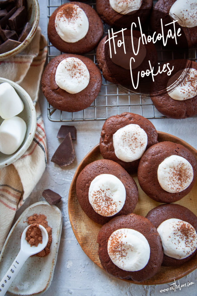 Hot Chocolate Cookies, a cookie that tastes like hot cocoa, sitting on a plate and a wire cooling rack, surrounded by ingredients for the cookie.