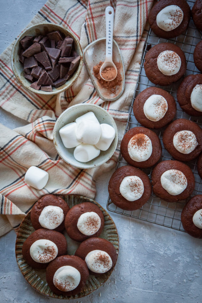 Hot Cocoa Cookies on a plate and a wire cooling rack, surrounded by ingredients like marshmallows, chopped chocolate and cocoa powder.