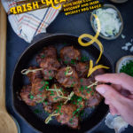 Irish Meatballs in a cast iron skillet, surrounded by some ingredients that are used in the recipe.