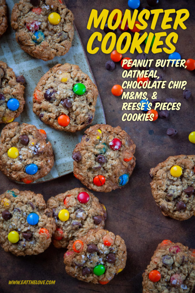 Monster Cookies on a table surrounded chocolate chips, m&m and reese's pieces candies.