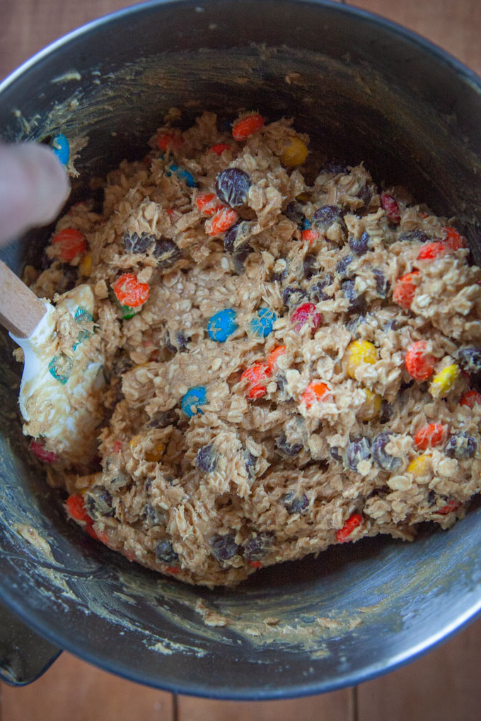 Hand mixing in chocolate chips, M&M and Reese's Pieces into the monster cookie dough.