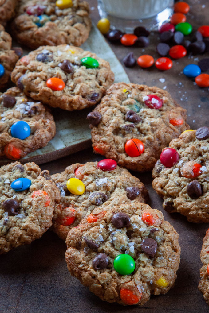 A pile of monster cookies on a table with chocolate chips, m&ms and reese's pieces in the background.