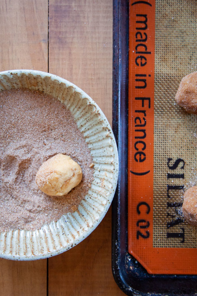 Rolling the pumpkin snickerdoodle cookie dough in the pumpkin-spice sugar mixture.