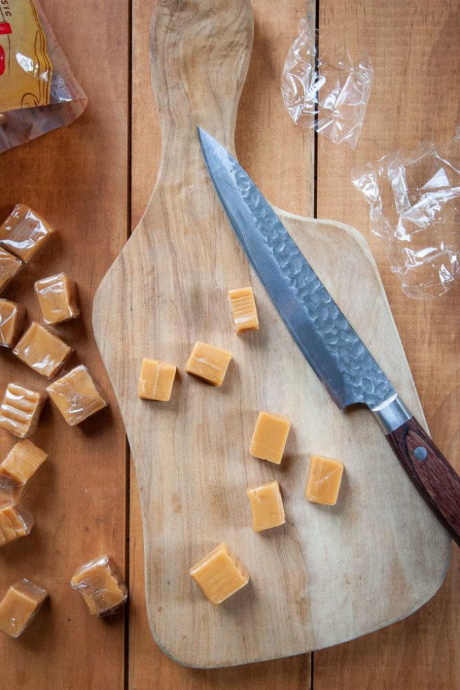 caramel candies cut in half on a cutting board.