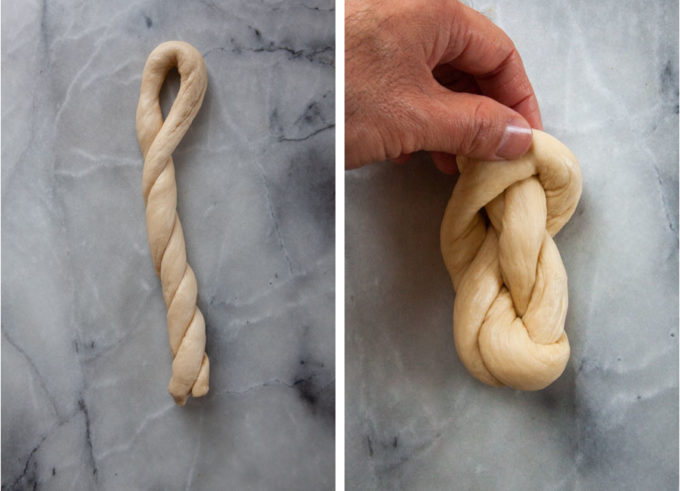 A hand forming the pretzel twist by pulling the dough into a knot.