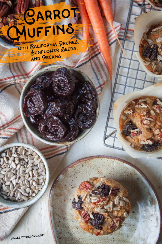 A carrot muffin with prunes, sunflower seeds and pecans on a plate with bowls of ingredients around it.