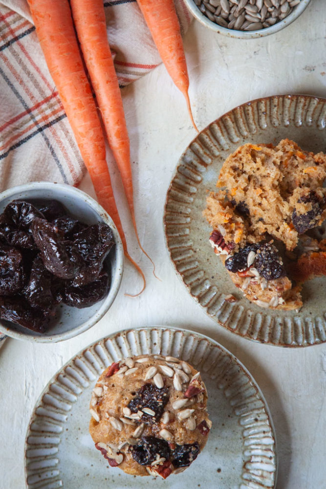 overhead photo of carrot muffins on a plates, with a bowl of prunes and some carrots next to them.