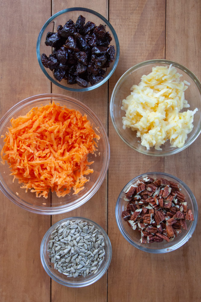Mix in ingredients for the carrot muffin, included shredded carrots, grated apples, prunes, sunflower seeds and pecans, all in bowls.