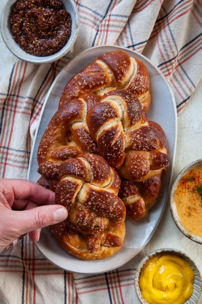 a hand grabbing a soft beer pretzel off a plate.