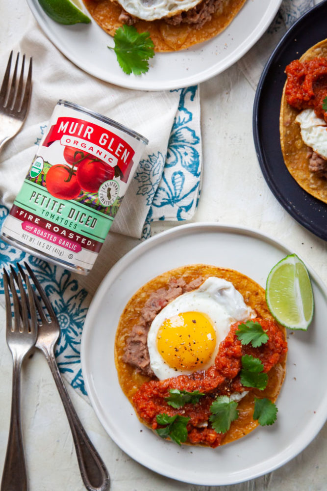 Huevos Rancheros (rancher egg tacos) on plates with a can of Muir Glen petite diced tomatoes next to the plate.