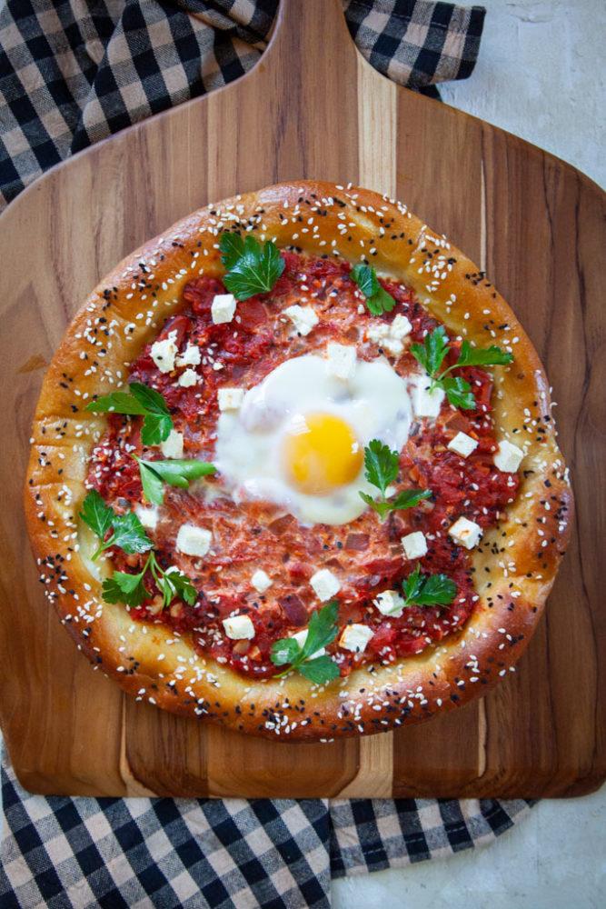 A pretzel shakshuka on a pizza peel.