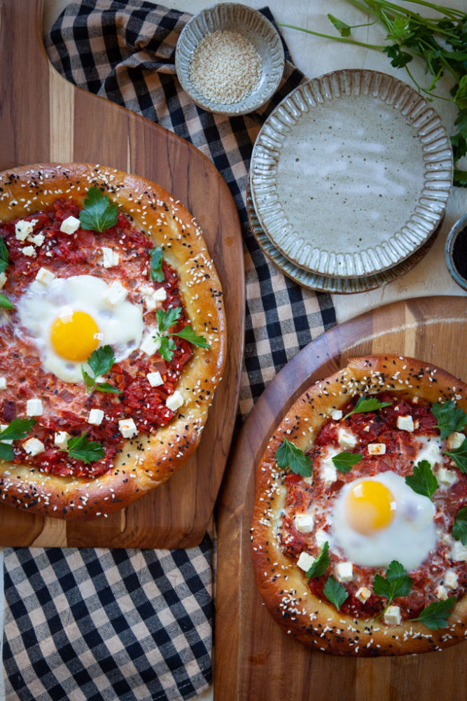 two pretzel shakshuka on a pizza peels next to small plates