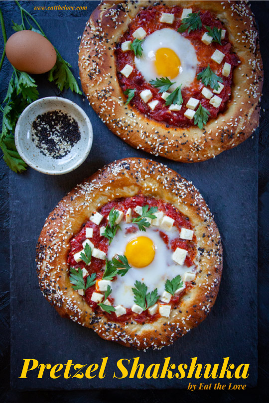 Two pretzel shakshuka sitting on a black slate surface with some ingredients next to it.